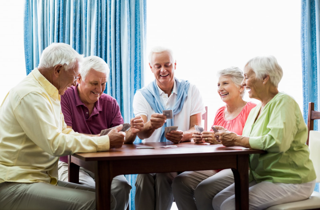 Independent living community members laughing and socializing over cards in a lounge area